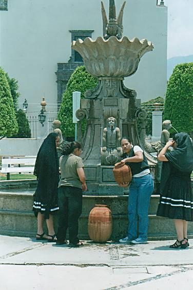 Zináparo, mujeres llevan agua, en sus cántaros, de la fuente céntrica