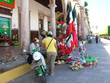 Puesto de banderitas a un costadod el monumento a Hidalgo